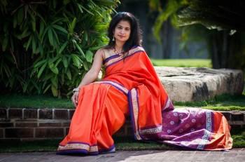 Orange Banarasi silk saree with navy blue border and pallu